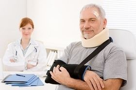 man in a sling and neck brace being treated by a doctor
